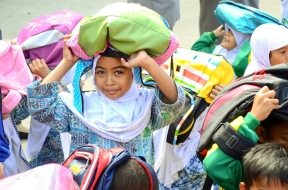 Intan, Grade 3, protects her head from falling debris. She is among the students from this northern Indonesian school huddling in the school court yard during a disaster drill. The drills help the 400+ students here learn to act quickly, protect themselves and help others during emergencies, thanks to training their teachers received after the 2004 tsunami. Ten years ago, the tsunami hit this school and wiped away all the buildings. It stole the lives of more than 250 students.